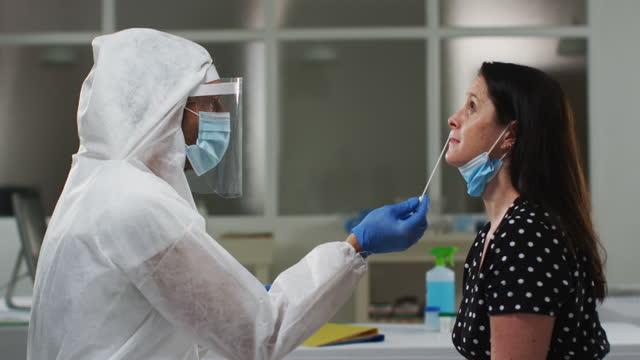 Medizinischer-Arbeiter-in-Schutzkleidung-unter-Tupfer-Test-von-Patientin