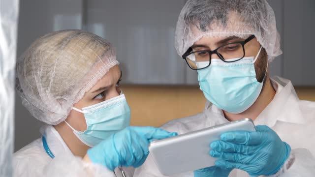 El-equipo-médico-de-médicos-con-batas-blancas-guantes-y-máscaras-protectoras-discuten-el-diagnóstico-de-los-pacientes-en-tabletas-digitales-en-el-hospital-Concepto-de-tratamiento-para-coronavirus-covid-19