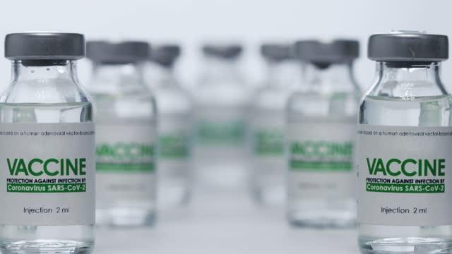 Las-botellas-de-la-vacuna-para-la-cura-del-coronavirus-COVID-19-se-encuentran-en-el-laboratorio-de-investigación-antes-de-la-inyección-Vacunación-ensayo-clínico-durante-la-pandemia-Flacones-viales-Amplia-macro-slider-dolly-out-shot-SARS-CoV-2-Na