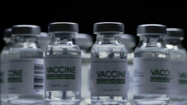 Las-botellas-de-vacuna-para-la-cura-del-coronavirus-COVID-19-se-rotan-rápidamente-en-el-laboratorio-de-investigación-Vacunación-inyección-ensayo-clínico-durante-la-pandemia-Viales-los-matraces-giran-en-el-sentido-de-las-agujas-del-reloj-Macro-an
