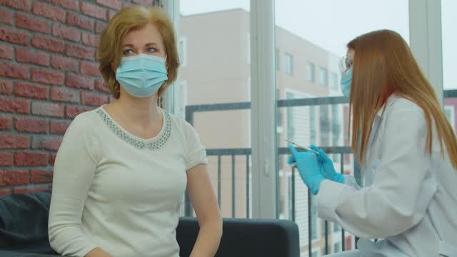 Enfermera-femenina-en-uniforme-inyectando-pacientes-varones-mayores-Médico-joven-inyectando-vacunas-contra-la-infección-por-covid-19-Medicina-tratamiento-salud-concepto-de-pandemia-Pandemia-de-coronavirus-