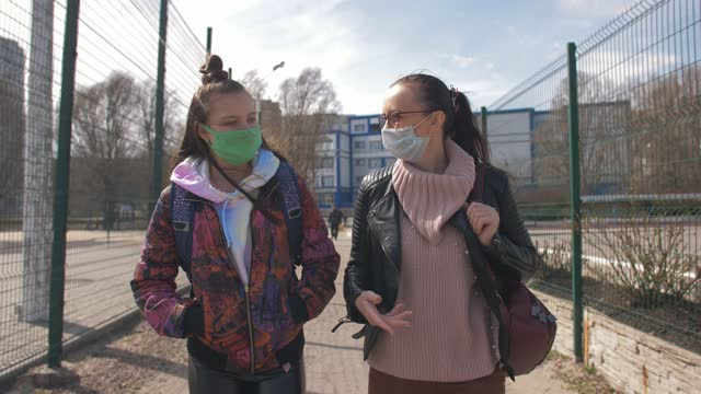 Mother-and-daughter-a-teenager-walking-down-the-street-in-protective-masks-