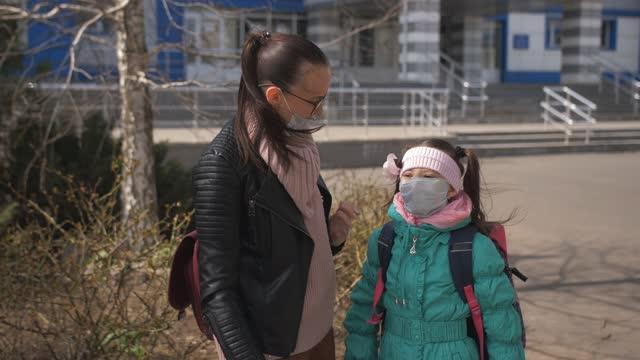 Una-madre-con-una-máscara-protectora-está-esperando-a-una-hija-pequeña-estudiante-de-primer-grado-de-la-escuela-después-de-la-escuela-Colegiala-estudiante-de-primer-grado-con-máscara-protectora-corre-hasta-mamá
