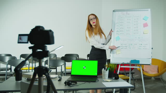 Teacher-recording-video-lesson-at-class-distance-education-schoolteacher-working-from-class-records-a-video-class-for-students-remote-online-learning-Green-Screen-Chroma-Key-Laptop-for-Learning-