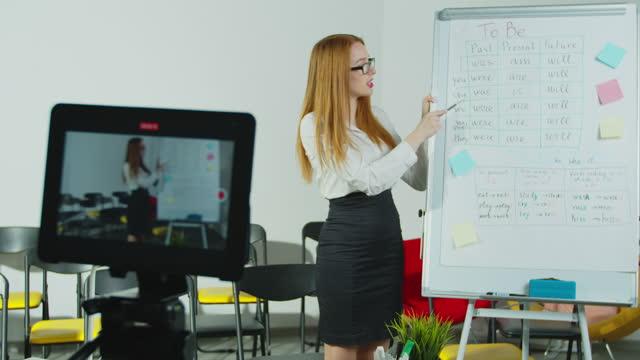 Profesora-que-tiene-clase-en-línea-Mujer-sonriente-hablando-con-los-estudiantes-a-través-de-videoconferencia-en-tablet-PC-Educación-remota-distanciamiento-social-prevención-de-cuarentena-