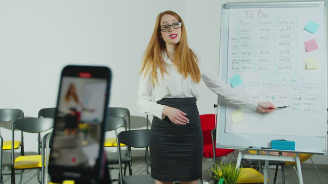 Smiling-woman-talking-to-students-via-video-conference-on-smartphone-Young-female-teacher-having-online-class-Remote-education-Social-distancing-quarantine-prevention-