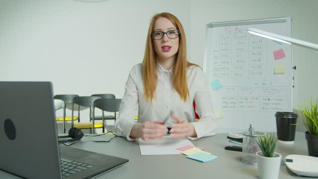 Profesor-de-inglés-profesor-de-enseñanza-virtual-mirar-webcam-dar-lección-de-distancia-La-tutora-de-la-escuela-explica-que-la-clase-en-línea-hablando-con-la-cámara-se-sienta-en-el-escritorio-en-el-salón-de-clases-Videoconferencia-llamar-a-la-educac