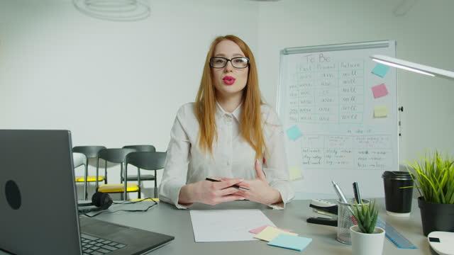 Lehrerin-Frau-die-online-in-der-leeren-Klasse-unterrichtet-Geschäftsfrau-vdo-rufen-Blick-auf-Kamera-Bildung-und-E-Learning-soziale-Abstand-und-Quarantäne-neue-Normalität-Arbeit-von-zu-Hause-Kommunikationskonzept-