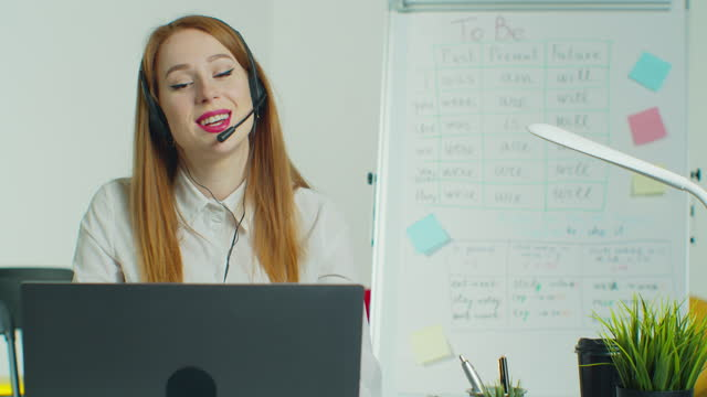 Woman-in-headphones-talking-to-students-via-video-conference-at-empty-class-Smiling-female-school-teacher-having-online-class-indoors-Education-concept-Quarantine-concept-Study-by-internet-