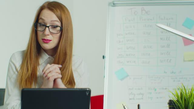 La-enseñanza-virtual-del-profesor-de-inglés-mira-a-tabletPC-dar-lección-a-distancia-La-tutora-de-la-escuela-explica-que-la-clase-en-línea-hablando-con-la-cámara-se-sienta-en-el-escritorio-en-el-salón-de-clases-Videoconferencia-llamar-a-la-educació
