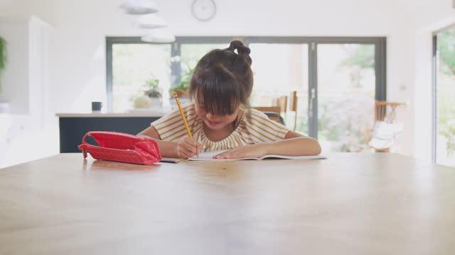 Joven-asiática-escuela-en-casa-trabajando-en-la-mesa-en-la-cocina-escribiendo-en-el-libro-durante-el-encierro