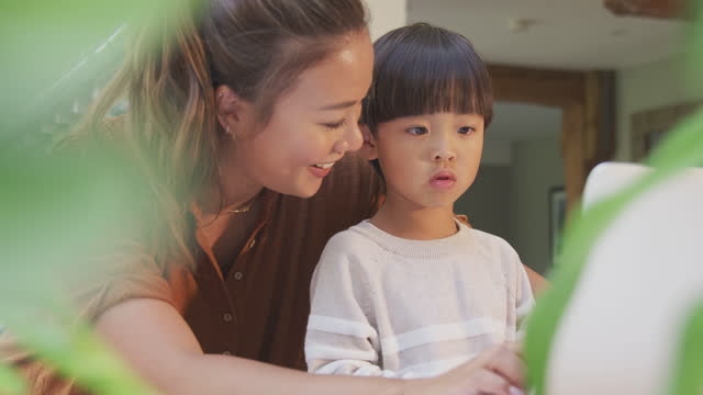Asian-Mother-Helping-Home-Schooling-Son-Working-At-Table-In-Kitchen-On-Laptop