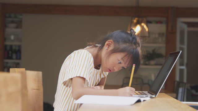 Young-Asian-Girl-Home-Schooling-Working-At-Table-Using-Laptop
