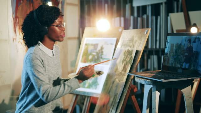 La-señora-africana-está-usando-un-tutorial-en-línea-para-pintar-una-imagen