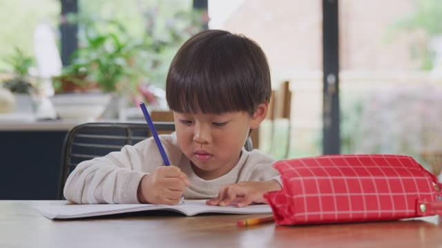 Los-jóvenes-asiáticos-que-escolaran-en-casa-trabajando-en-la-mesa-en-la-cocina-escribiendo-en-el-libro-durante-el-encierro
