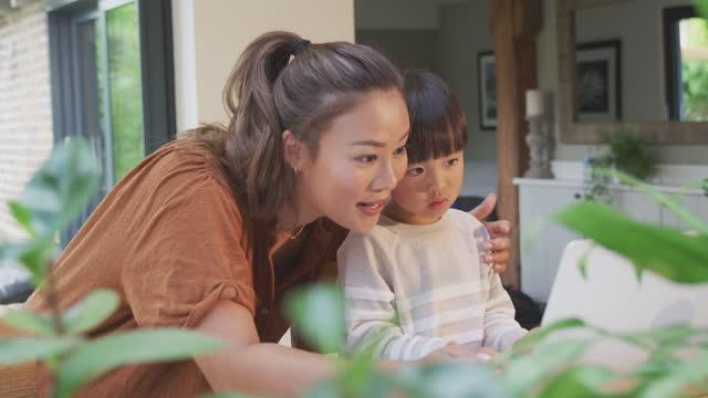 Asiatische-Mutter-hilft-zu-Hause-Schulbildung-Sohn-arbeiten-am-Tisch-in-Küche-auf-Laptop