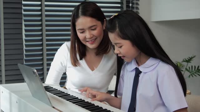 Beautiful-mother-looking-her-daughter-playing-piano-at-home-She-was-delighted-that-her-daughter-could-play-the-piano-