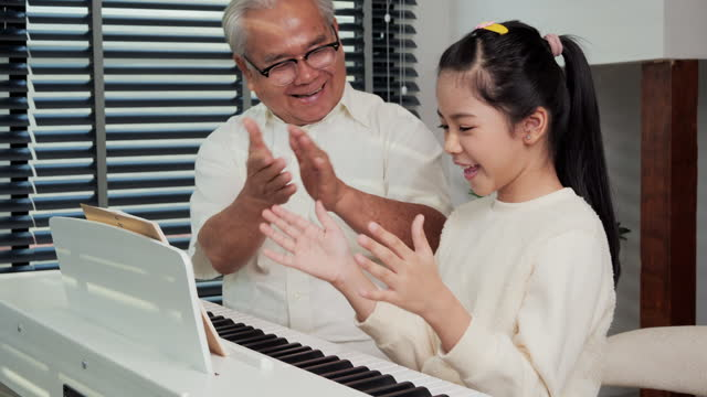 Grandfather-looking-granddaughter-playing-piano-at-living-room-She-was-showing-play-piano-to-Grandfather-with-confident-