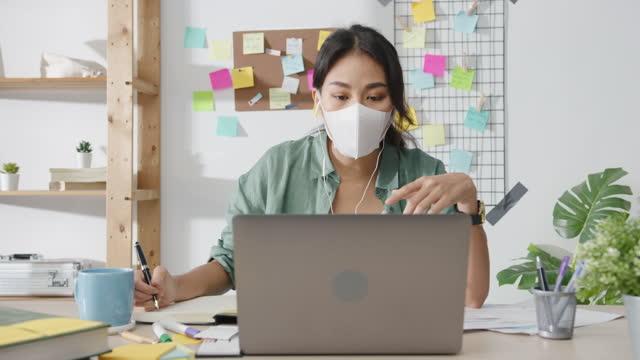 Asiatische-Geschäftsfrau-trägt-medizinische-Gesichtsmaske-mit-Laptop-sprechen-mit-Kollegen-über-Plan-in-Videoanruf-während-der-Arbeit-von-zu-Hause-aus-im-Wohnzimmer-