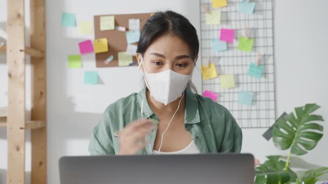 La-empresaria-asiática-que-usa-máscara-facial-médica-usando-computadoras-portátiles-habla-con-sus-colegas-sobre-el-plan-en-videollamada-mientras-trabaja-desde-casa-en-la-sala-de-estar-