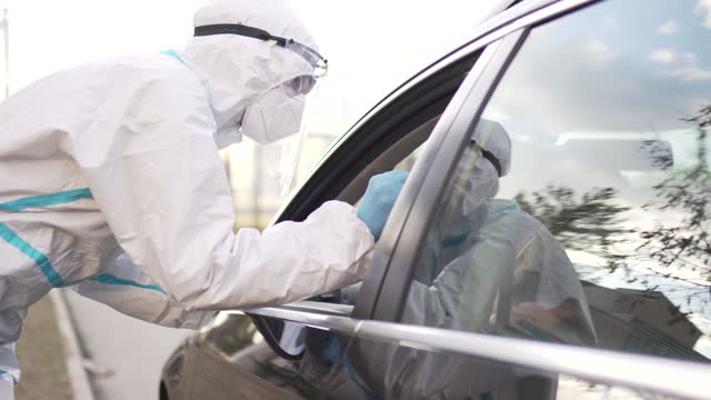 Healthcare-worker-doing-PCR-testing-on-Covid-19-from-patient-in-car