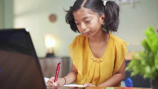 Concept-of-homeschooling-online-education-or-e-learning-young-girl-busy-in-writing-by-looking-into-laptop-while-teacher-explaining-during-class