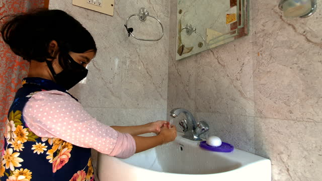 Masked-girl-Washing-hands-with-soap-and-water-and-using-alcohol-based-hand-rub-kills-viruses-