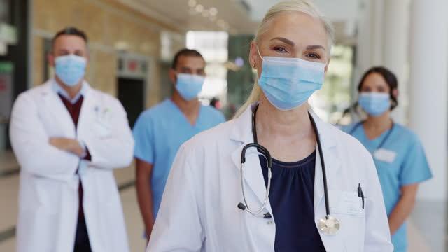 Zufriedener-Oberarzt-trägt-Gesichtsmaske-mit-Team-im-Hintergrund