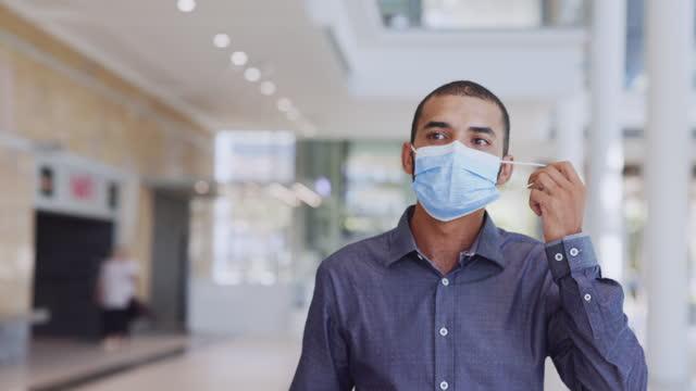 Hombre-inmunizado-satisfecho-quitándose-la-máscara-facial-después-de-la-vacunación