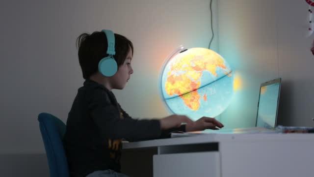 Hermoso-niño-con-auriculares-usando-computadora-portátil-mientras-estudia-en-el-escritorio-en-casa-durante-el-coronavirus