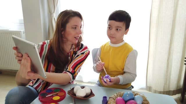 Cute-child-painting-eggs-learning-via-computer-at-home