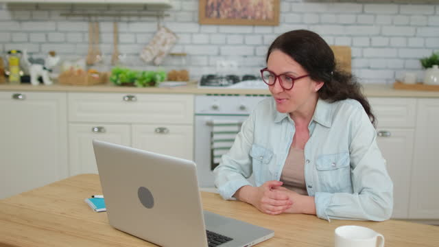 Webcam-chat-meeting-video-call-concept-Smiling-laughing-woman-girl-talking-online-chatting-with-friends-social-media-using-laptop-computer-at-home-kitchen-Coronavirus-COVID-19-cuarentena-4K-slow-mo