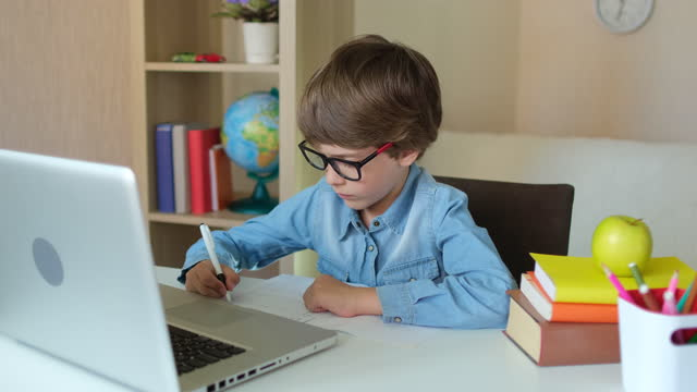 Child-Boy-Kid-schoolboy-in-glasses-using-tablet-laptop-computer-for-school-homework-studying-at-home
