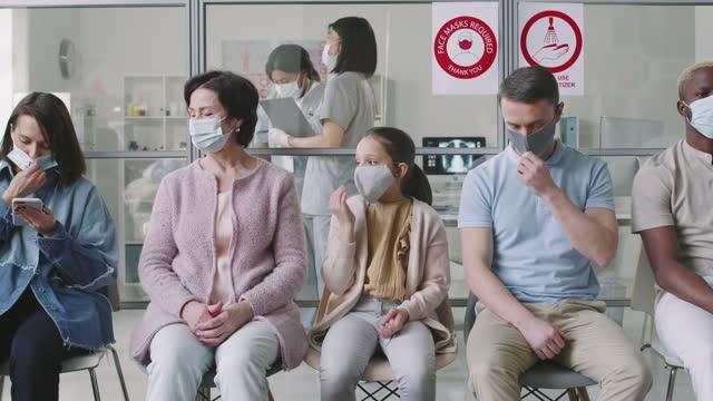 Personas-diversas-con-máscaras-esperando-en-la-cola-del-hospital