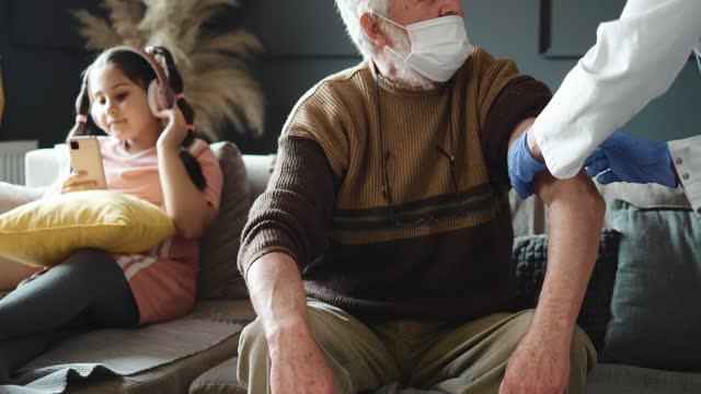 Female-doctor-visiting-senior-man-giving-her-vaccination-both-wearing-face-masks-retirement-health-care-at-home-Grandfather-and-granddaughter-in-isolation-Vaccination-of-pensioners-at-home