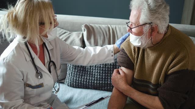 El-médico-rellena-la-documentación-después-de-vacunar-al-abuelo-Personas-mayores-en-la-vanguardia-de-la-vacunación-COVID-19