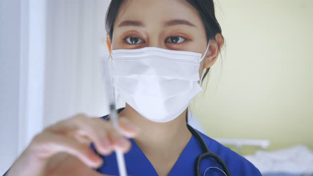 Close-up-of-female-Asian-doctor-holding-a-vaccine-injection-needle-ready-for-vaccination-Young-medical-lab-technicia-at-work