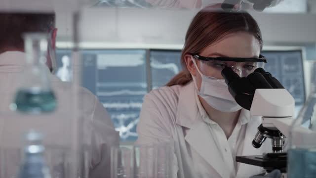 Diversos-científicos-estudiando-el-modelo-de-esqueleto-humano-Uso-de-computadoras-y-microscopios-Discutiendo