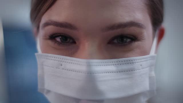 Ärztin-trägt-Maske-im-Labor-Zufrieden-mit-ihrer-Arbeit-Lächelnd-in-eine-Kamera