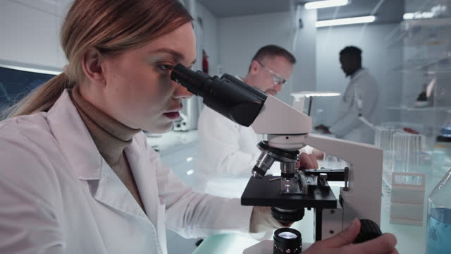 Diverse-scientists-studying-medical-samples-Using-computers-and-microscopes-Modern-laboratory-interior