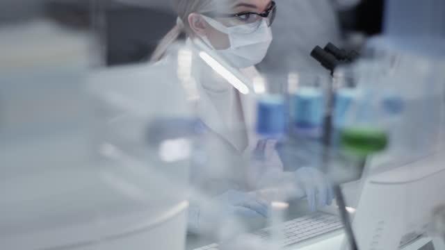 Diverse-Wissenschaftler-untersuchen-medizinische-Proben-Verwendung-von-Computern-und-Mikroskopen-Modernes-Labor-Interieur