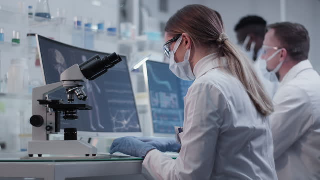 Diverse-scientists-studying-human-skeleton-model-Using-computers-and-microscopes-Discussing