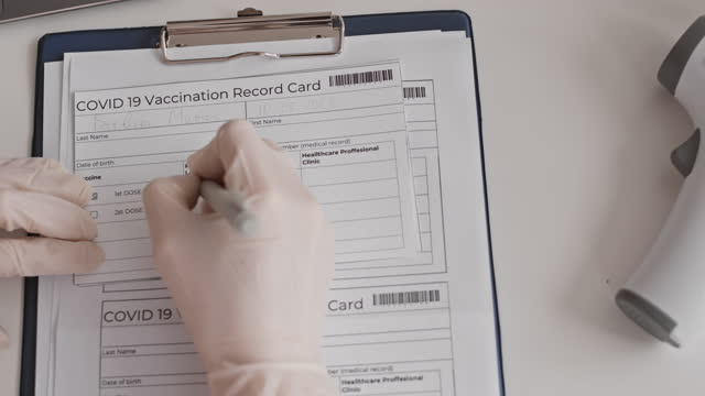 Hand-Filling-in-Vaccination-Record-Card