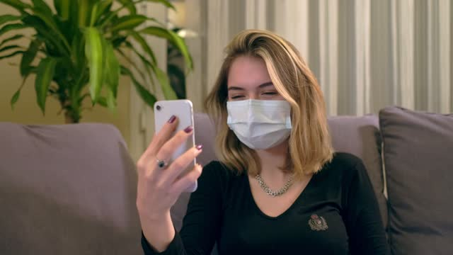 Young-Turkish-woman-with-a-facial-mask-having-a-video-call-on-her-smartphone-while-sitting-on-the-sofa-There-is-a-laptop-computer-on-her-lap-coffee-cup-and-a-hand-sanitizer-bottole-on-the-table-