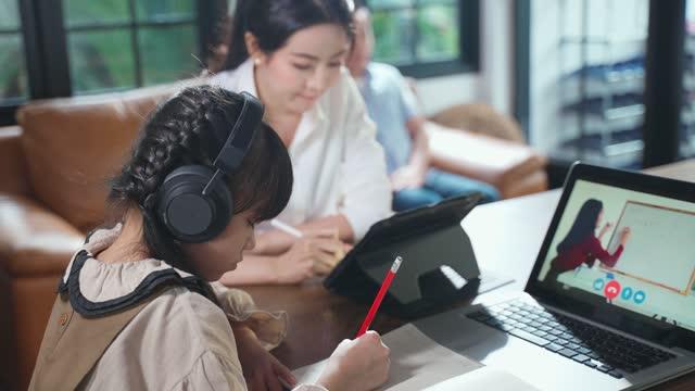 Educación-en-casa-niña-asiática-que-aprende-en-línea-clase-de-maestro-de-escuela-por-reunión-digital-remota-de-Internet-debido-a-la-pandemia-de-coronavirus-Niño-buscando-la-pantalla-del-ordenador-portátil-con-ayuda-de-la-madre-