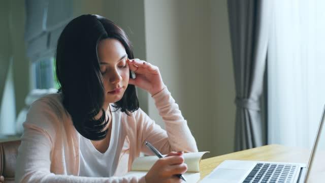 Joven-caucásica-sentada-sola-en-la-sala-de-estar-Mujer-que-se-siente-aburrida-y-cansada-causa-de-dolor-de-cabeza-por-efecto-del-bloqueo-del-gobierno-de-Coronavirus-o-crisis-pandémica-COVID-19-