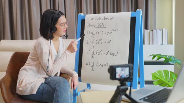Asian-school-young-woman-teacher-working-from-home-teach-online-math-subject-to-student-studying-from-home-Girl-points-on-whiteboard-talk-on-headphone-Remote-education-class-during-covid19-pandemic