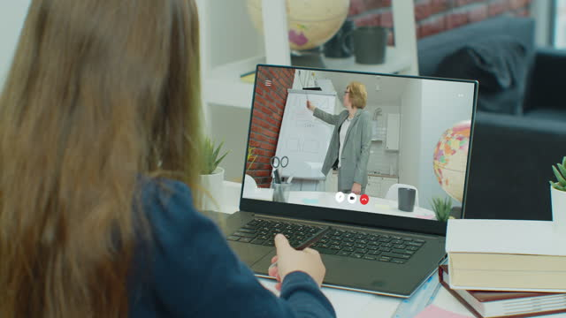 Teen-girl-school-college-student-study-distance-learning-talk-with-online-teacher-on-laptop-screen-write-notes-Elearning-video-call-videoconference-class-with-tutor-