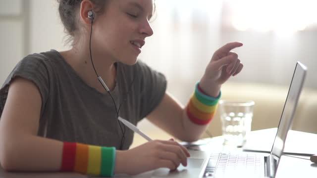 La-joven-colegiala-tiene-una-lección-en-línea-remotamente-Chica-hablando-usando-auriculares-y-computadora-portátil-concepto-de-videollamada