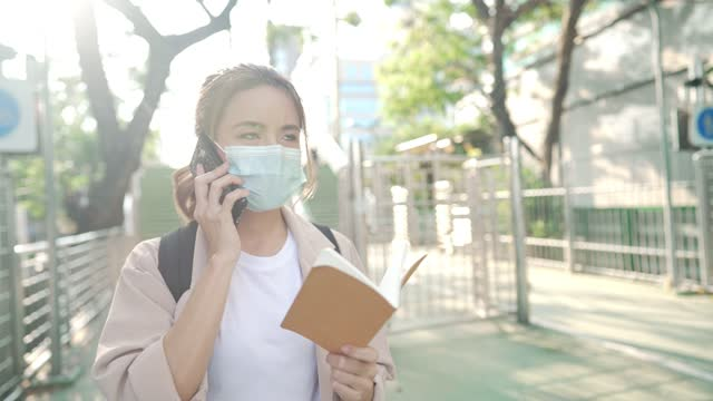 Attractive-student-with-a-small-note-on-hand-talking-on-the-phone-in-the-university-concept-of-unlimited-wireless-education